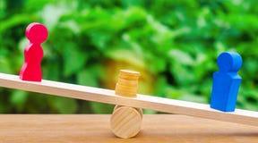 De houten cijfers van een man en een vrouw bevinden zich op de schalen en de muntstukken tussen hen het concept het geslacht beta stock fotografie