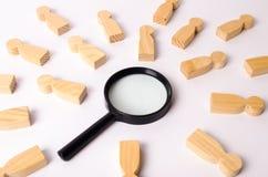De houten cijfers van mensen liggen rond een vergrootglas op een witte achtergrond Het concept het onderzoek naar mensen en arbei stock foto