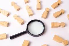 De houten cijfers van mensen liggen rond een vergrootglas op een witte achtergrond Hurend voor het werk, vindende mensen Stock Afbeeldingen