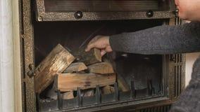 De houten close-upfoto van de mens die opent open haard bij woonkamer het programma zetten royalty-vrije stock afbeeldingen