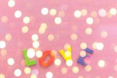De houten colotful liefdebrief op de roze gift verpakte document als achtergrond met exemplaarruimte stock fotografie