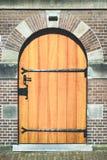 De houten deur in het baksteenhuis Stock Afbeelding