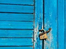 De houten deur met schil blauwe verf is gesloten met een hangslot stock afbeelding