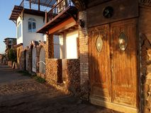 de houten deur van het gebouw en de zonovergoten kant van de straat in een Egyptisch dorp bij zonsopgang royalty-vrije stock foto's