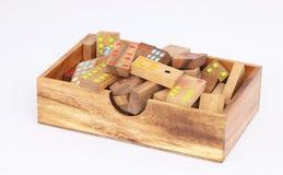 De houten die dominostukken maken omhoog een domino in de houten doos op wit wordt geplaatst Royalty-vrije Stock Fotografie