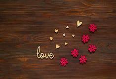 De houten harten met inschrijving houden van en decor van bloemen op een houten achtergrond, concept feestelijke samenstelling, v Stock Afbeeldingen