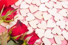 De houten harten op roze achtergrond hebben een bloem toenamen royalty-vrije stock foto