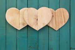 De houten harten van liefdevalentijnskaarten op turkoois geschilderde achtergrond Stock Foto's