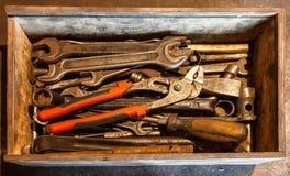 De houten hulpmiddeldoos van handhulpmiddelen met oude en vuile, roestige moersleutels, ringsmoersleutels, buigtang, schroevedraa Stock Foto's