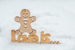 De houten inschrijvingsliefde is op de sneeuw, boven het is een houten mens Stock Afbeeldingen