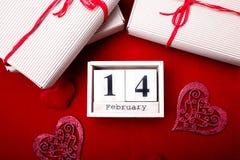 De houten kalender toont van 14 Februari met rode hart en giftdozen Royalty-vrije Stock Foto