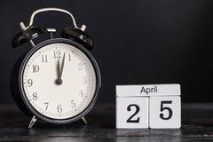 De houten kalender van de kubusvorm voor 25 April met zwarte klok Royalty-vrije Stock Fotografie