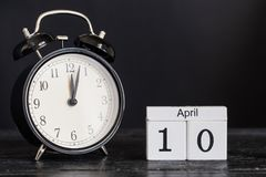 De houten kalender van de kubusvorm voor 10 April met zwarte klok Royalty-vrije Stock Foto