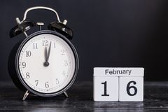 De houten kalender van de kubusvorm voor 16 Februari met zwarte klok Royalty-vrije Stock Foto
