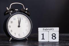 De houten kalender van de kubusvorm voor 18 Februari met zwarte klok Stock Foto's