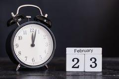 De houten kalender van de kubusvorm voor 23 Februari met zwarte klok Stock Foto's
