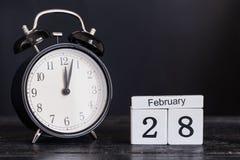 De houten kalender van de kubusvorm voor 28 Februari met zwarte klok Stock Foto's