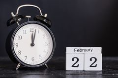 De houten kalender van de kubusvorm voor 22 Februari met zwarte klok Royalty-vrije Stock Afbeelding