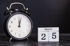 De houten kalender van de kubusvorm voor 25 Maart met zwarte klok Stock Fotografie