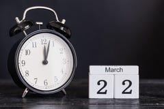 De houten kalender van de kubusvorm voor 22 Maart met zwarte klok Royalty-vrije Stock Afbeeldingen