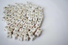 De houten kubussen met brieven van het Engelse alfabet liggen op een witte achtergrond Het leren en geletterdheid royalty-vrije stock foto