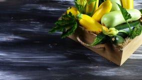 De houten lade met verse courgette komt en groene bladeren op een donkere achtergrond tot bloei Verse product-groenten vegetables Royalty-vrije Stock Foto