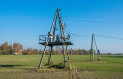 De houten lijnen met hoog voltage van de steunenmacht tegen de blauwe hemel De elektro industrie royalty-vrije stock afbeelding
