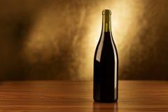 De houten lijst van rode wijnflessen en gouden achtergrond Stock Foto's