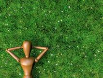 De houten mens is ontspant in ingediend van gras. royalty-vrije illustratie