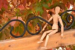 De houten mens zit op de bank onder rode bladeren stock foto's