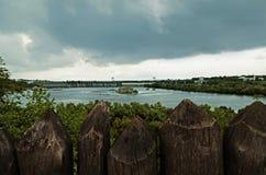 De houten palissade bevindt zich tegen de achtergrond van een hydro-elektrische dam onder een donkere stormachtige hemel stock afbeeldingen