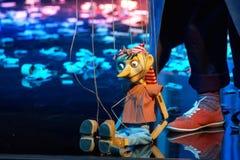De houten Pinocchio-pop zit op de vloer royalty-vrije stock afbeeldingen