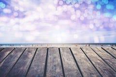 De houten portiek door het overzees heeft bokeh verlichting in het water Ga de zomer in royalty-vrije stock fotografie