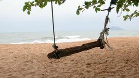De houten schommeling met het strand overzeese van het kabel bijna zand kust vóór onweer komst stock footage
