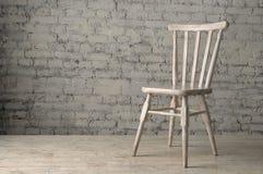 De houten stoel bevindt zich op houten vloer tegen de achtergrond van een bakstenen muur Royalty-vrije Stock Foto's