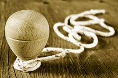 De houten tol met een koord rolde in zijn as, in sepia t Stock Foto