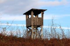 De houten toren van de de jachtobservatie met geïmproviseerde ladders bovenop kleine heuvel die met hoog droog gras en dichte veg royalty-vrije stock afbeelding