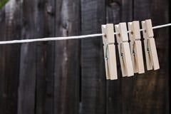 De houten wasknijpers hangen op een kabel op een houten achtergrond stock foto