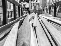 De houten zwart-witte gezaagde natuurlijke bouwraad plakt logboeken met knopen op een rek bij een zaagmolen in een opslag De acht stock fotografie