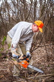 De houthakker gebruikt zijn kettingzaag sneed de boom Royalty-vrije Stock Afbeeldingen