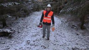 De houthakker met kettingzaag en benzine kan op bosweg stock footage