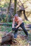 De houthakker snijdt een boomstam met een bijl Stock Afbeeldingen