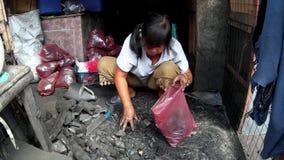 De houtskool van de vrouwenverpakking in plastic zak aan de kant van de straat toe te schrijven aan gebrek aan marktfaciliteiten stock video