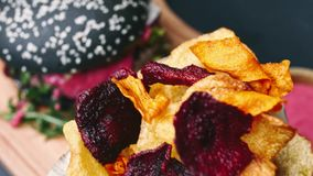 De houtskoolhamburger met frieten en de rode die saus zijn op de raad, met een mes wordt doordrongen, en klaar om in 4k te eten stock videobeelden