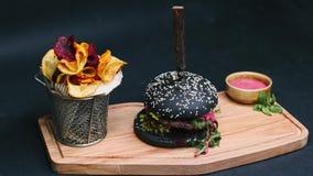 De houtskoolhamburger met frieten en de rode die saus zijn op de raad, met een mes wordt doordrongen, en klaar om in 4k te eten stock footage