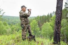 De houtvester kijkt door verrekijkers stock fotografie