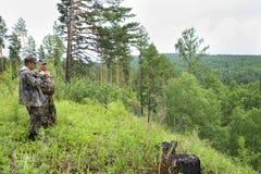 De houtvester kijkt door verrekijkers stock foto's