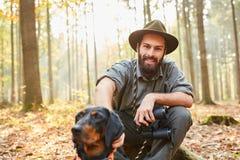 De houtvester met jachthond en verrekijkers neemt een onderbreking stock foto's