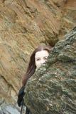 De huid - en - zoekt: het langharige donkerbruine meisje verbergt achter een rots op een strand stock foto's