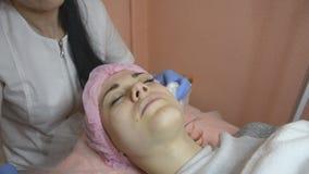 De huid van Cosmetologistoneffenheden van gezicht aan vrouwelijke pati?nt een intensieve procedure stock video
